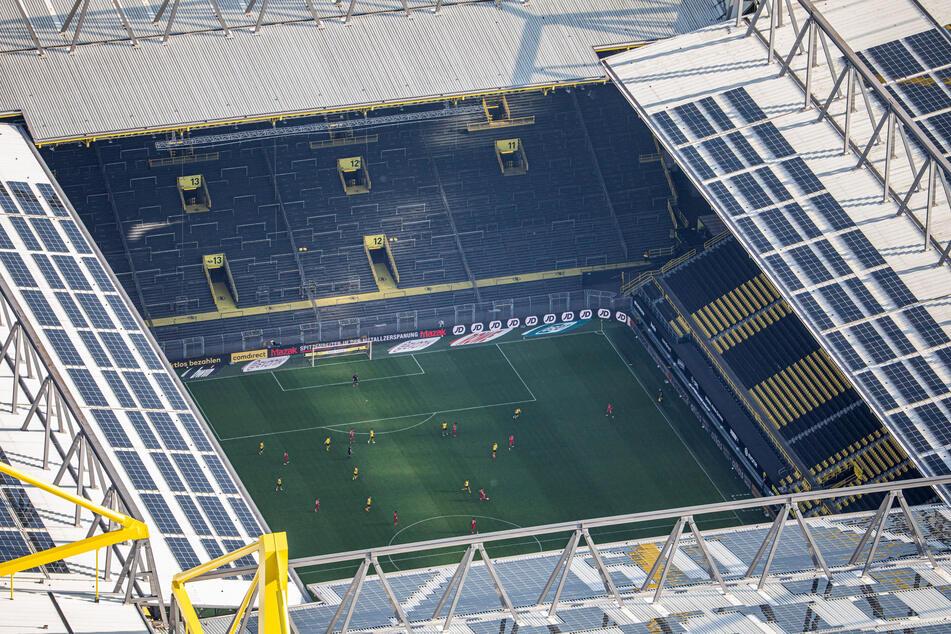 Fußballer zweier Mannschaften (Dortmund in gelb) bestreiten eine Partie vor leeren Zuschauerrängen.