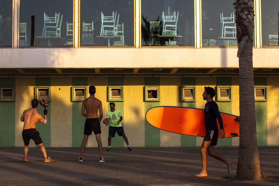 Israel, Tel Aviv: Männer spielen Paddelball neben einem geschlossenen Hotel. Das Land befindet sich in einem dreiwöchigen Lockdown aufgrund der Corona-Pandemie.