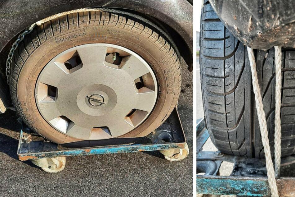 Ein Mann hat in Berlin-Wedding das Hinterrad seines Autos mit Ketten und Seilen auf einem Rollbrett fixiert.