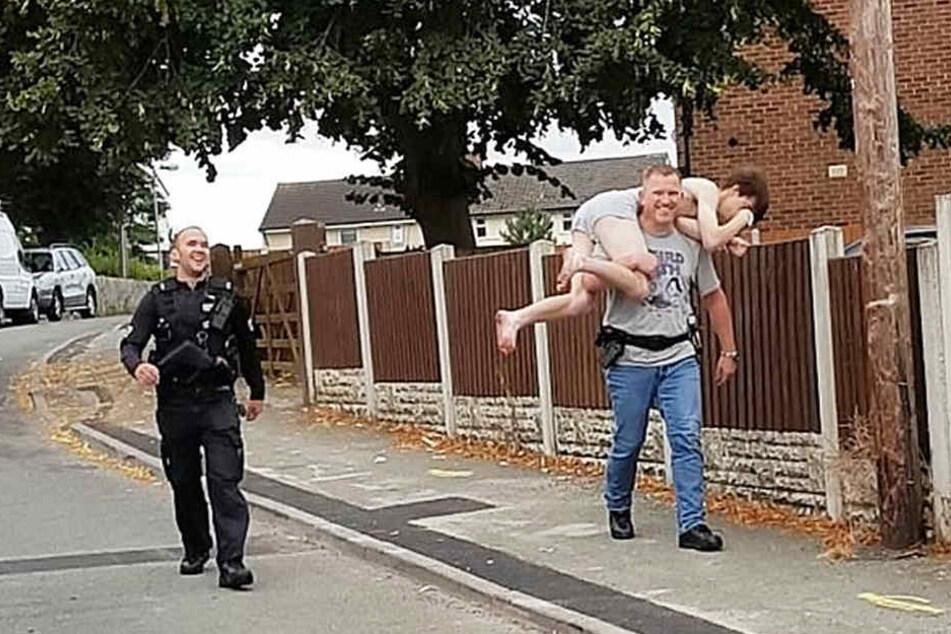 Hier nimmt ein grinsender Polizist einen Mann in Unterhose auf die Schultern