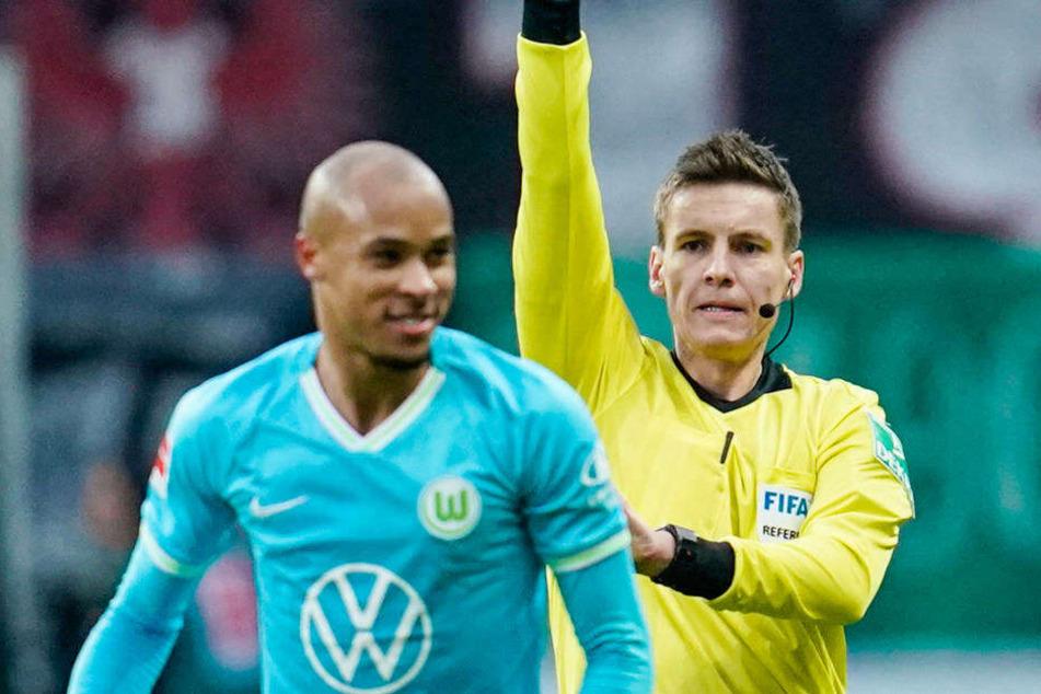 Schiedsrichter Daniel Siebert zeigt Wolfsburgs Marcel Tisserand die gelbe Karte, kurz danach sah der Verteidiger gelb-rot.