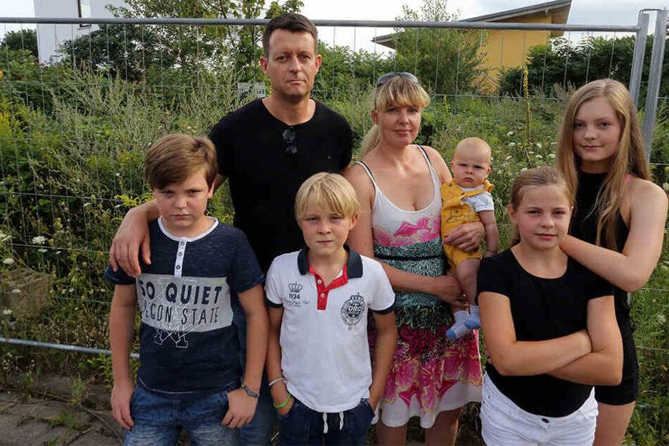 Familie Schirmer vor ihrem Baugrundstück. Mit der Familienförderung der SAB sind sie recht unglücklich. Sie müssen ihr Haus teuer auf dem freien Markt finanzieren.