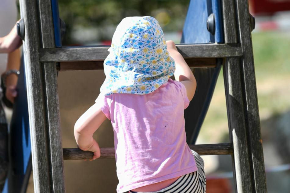 Ein Mädchen geht auf dem Spielplatz einer Kita eine Rutsche hoch.