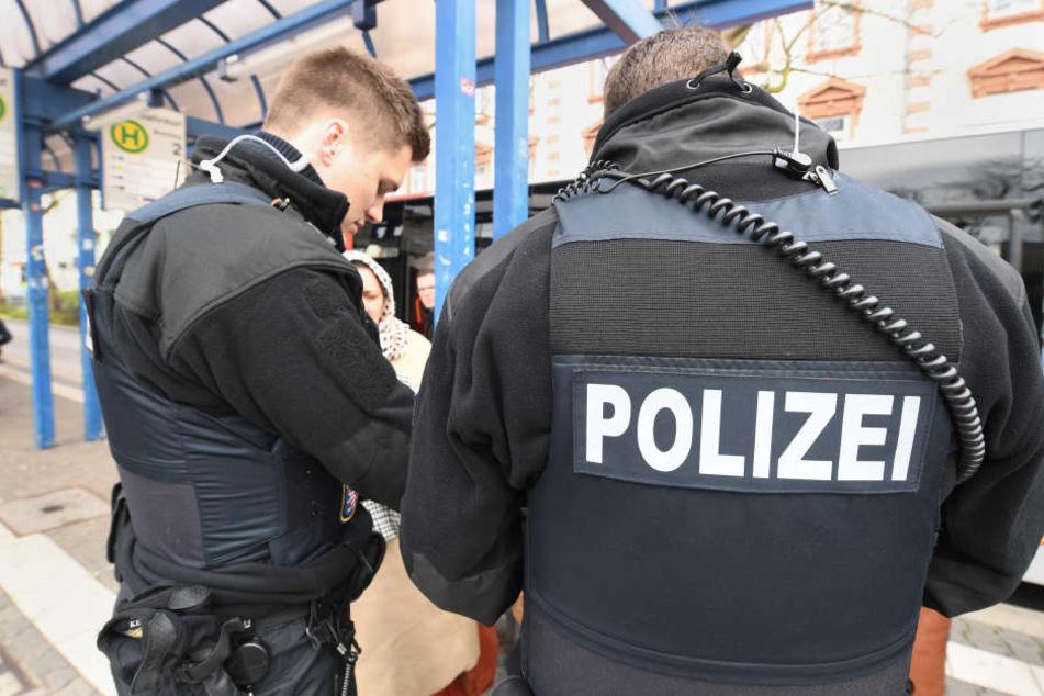 Polizisten stehen während einer Fahrkartenkontrolle an einer Bushaltestelle. (Symbolbild)