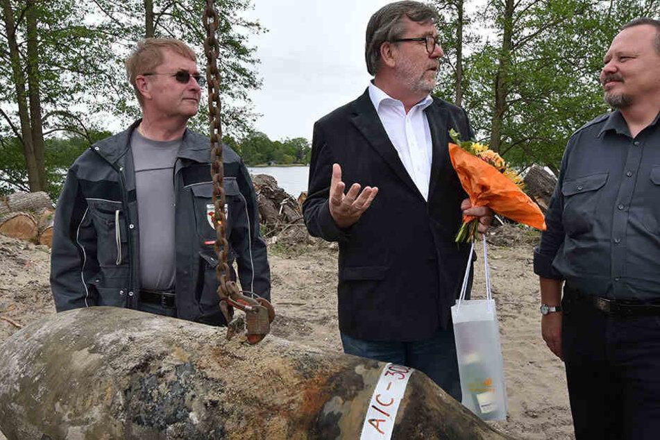 Oranienburgs Bürgermeister Hans-Joachim Laesicke (mi.) überreicht am 12.05.2015 in Oranienburg Blumen an die Sprengmeister Andre Müller (r.) und Heino Borchert. Die Bombe wurde am Ufer des Lehnitzsees gefunden.