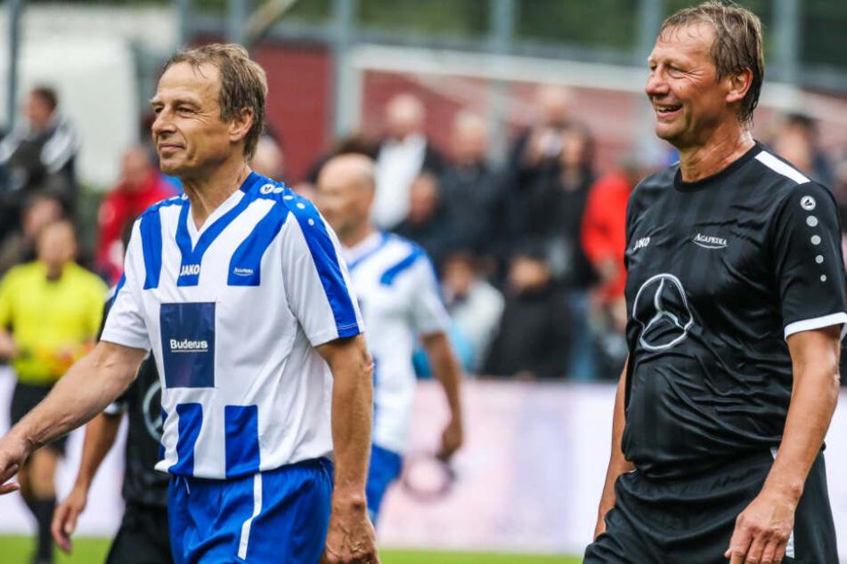 Baden-Württemberg, Geislingen an der Steige: Fußball: Benefizspiel mit Altstars im TG-Stadion. Jürgen Klinsmann (l) läuft zusammen mit Guido Buchwald vom Spielfeld.