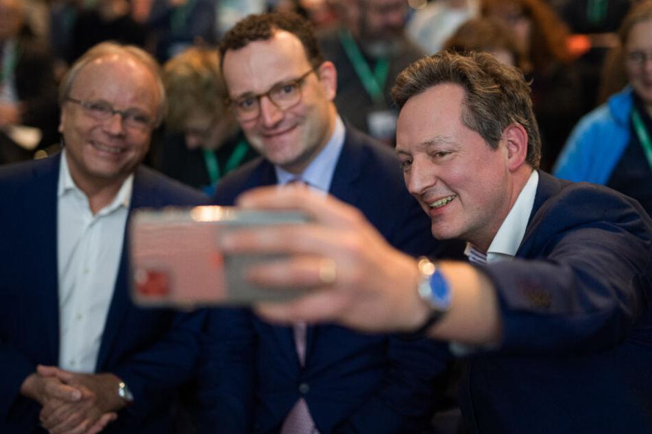 Eckart von Hirschhausen (r.) macht bei dem Kongress schnell noch ein Selfie mit dem Bundesgesundheitsminister Jens Spahn (M.).