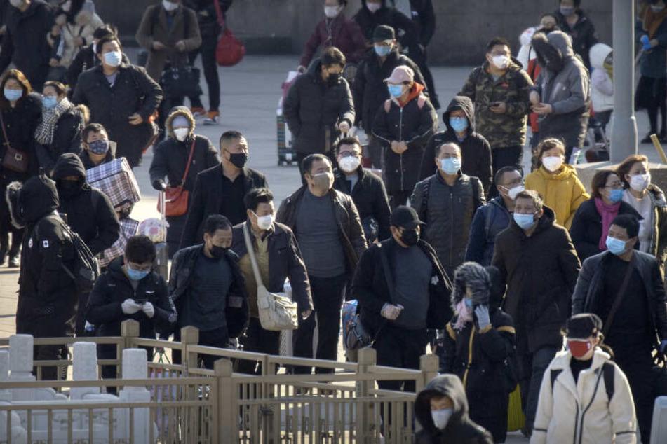 Reisendetragen Mundschutz, während sie vor dem Pekinger Bahnhof entlang gehen.