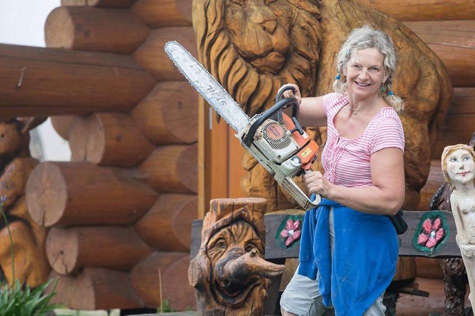 Schnittig: Karen Hobelsberger schwingt die Säge auf der Bank vor ihrer Blockhütte.