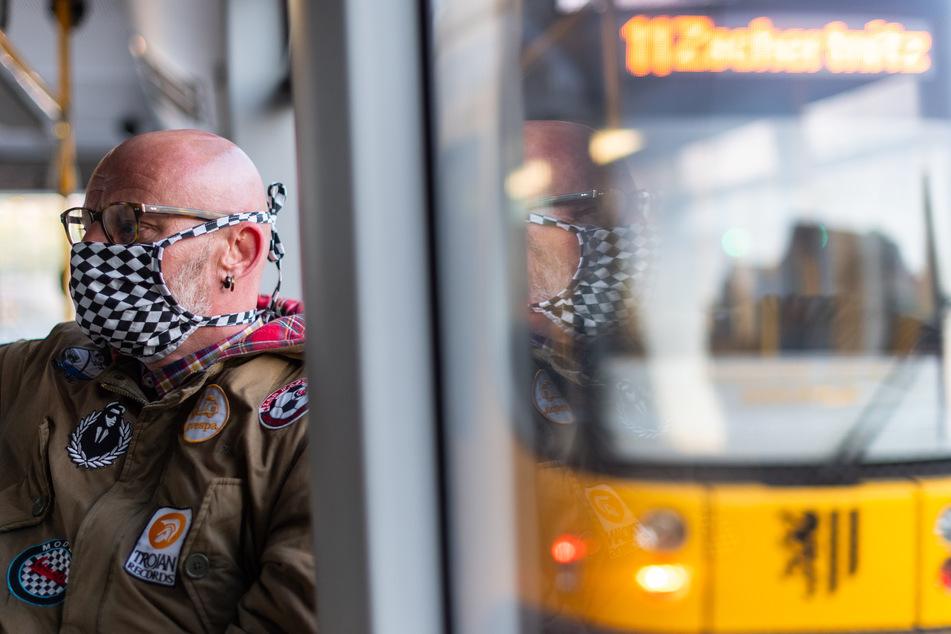 Michael Riedel, Gesundheits- und Krankenpfleger, sitzt am Morgen auf dem Weg zur Arbeit in einer Straßenbahn und trägt einen Mundschutz.