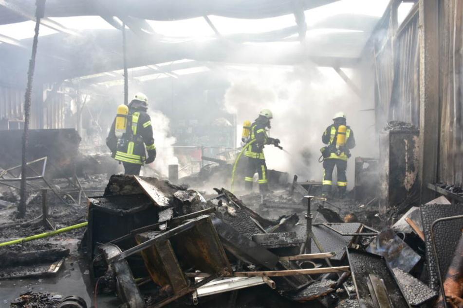 Feuerwehrleute bei der Arbeit in der abgebrannten Lagerhalle.