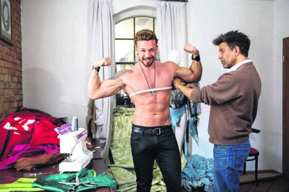 Stripper Damian (l.) spannt die Muckis an, damit Dyona Lorr ordentlich Maß nehmen kann.