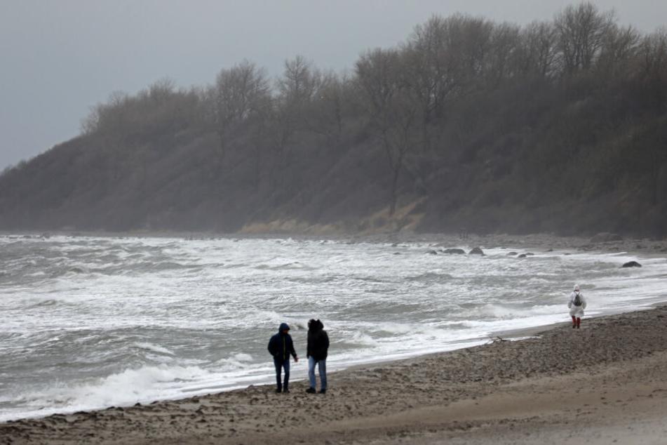 Spaziergänger sind an der aufgepeitschten Ostsee in Rerik unterwegs.