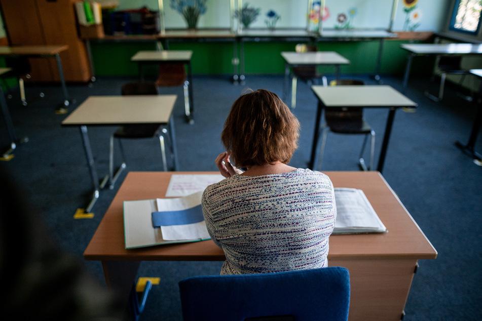 Eine Lehrerin sitzt am Pult im Klassenraum.