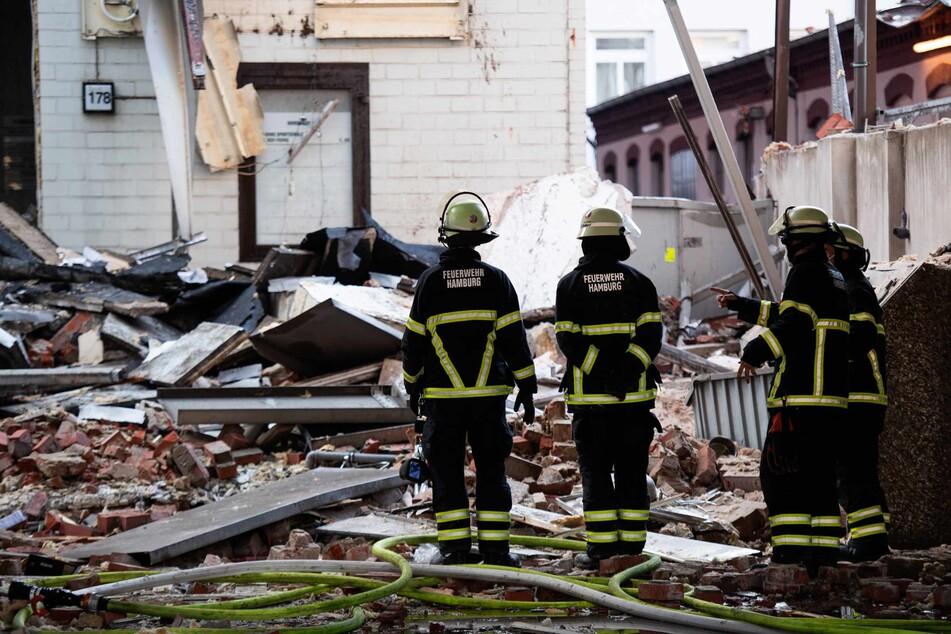 Einsatzkräfte der Feuerwehr stehen vor den Trümmern.