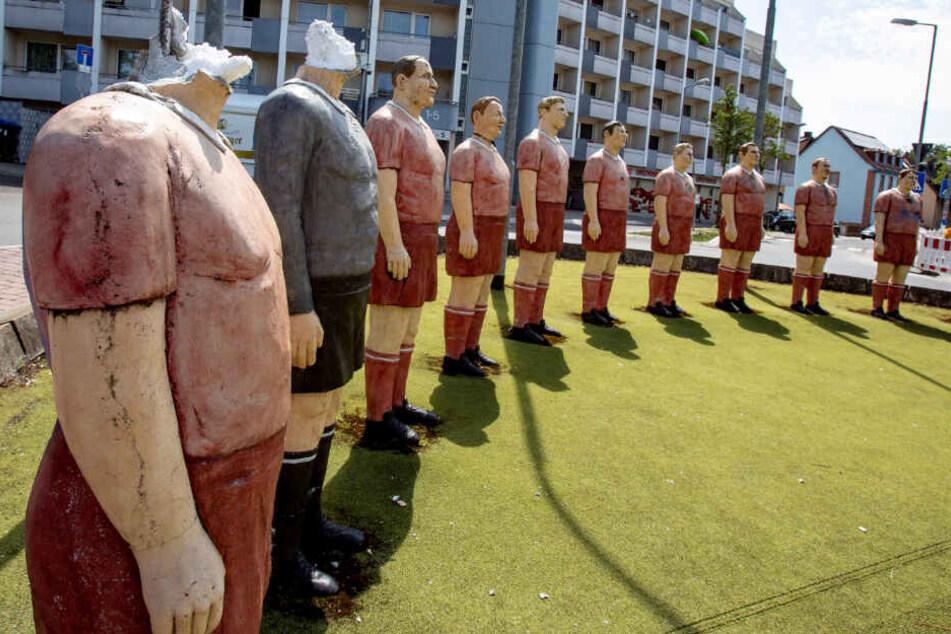 Zwei Fußballerfiguren des sogenannten Elf-Freunde-Kreisels stehen mit abgeschlagenen Köpfen auf dem Rasen der Verkehrsinsel.