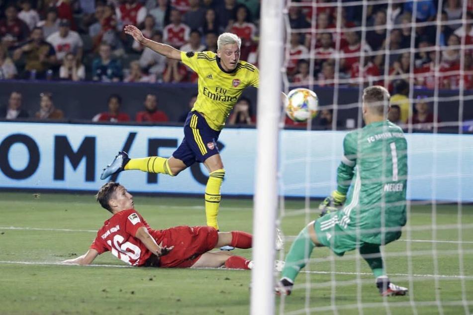 Münchens Jonas Kehl (l) und Torhüter Manuel Neuer (r) gegen Arsenals Mesut Özil.