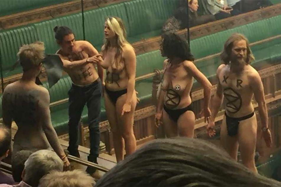 Die Aktivisten stehen nackt auf der Besuchertribüne in Westminster.