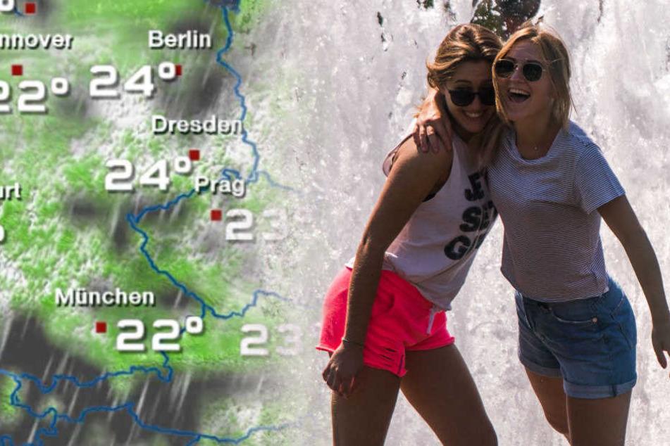 Zwei junge Touristinnen holen sich im Brunnen am Lustgarten etwas Abkühlung.