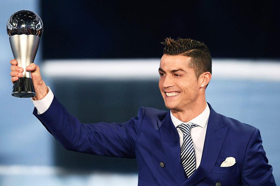 Stolz reckt Cristiano Ronaldo den Pokal als bester Fußballer der Welt nach oben.