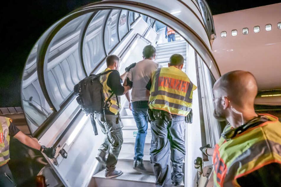 Ein Mann geht in Begleitung zweier Beamter den Aufgang zum Flugzeug hoch (Symbolfoto).