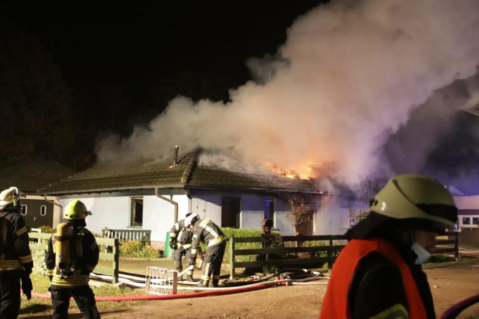Feuerwehrkräfte löschen ein in Brand stehendes Einfamilienhaus in Werneuchen (Landkreis Barnim).