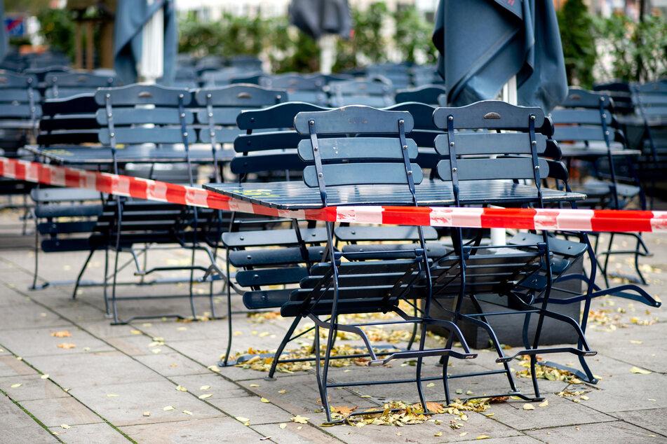 Tische und Stühle stehen vor einem geschlossenen Restaurant.