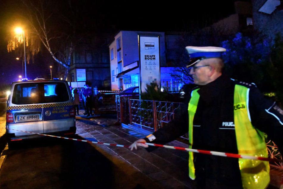 Ein Polizist sichert den Escape Room ab. Durch einen Brand sind fünf Jugendliche gestorben.