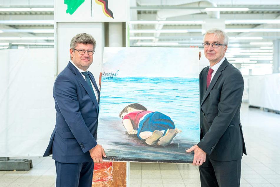 Zeugnis der Flüchtlingskrise: DRK-Chef Rüdiger Unger (55.,l.) übergab dieses Bild an Sammlungsleiter Dietmar Preißler (60).