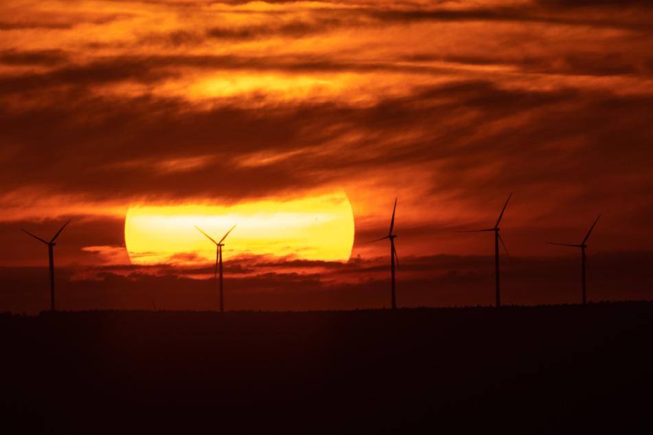 Baden-Württemberg, Ochsenwang: Die Sonne geht über Windrädern auf.
