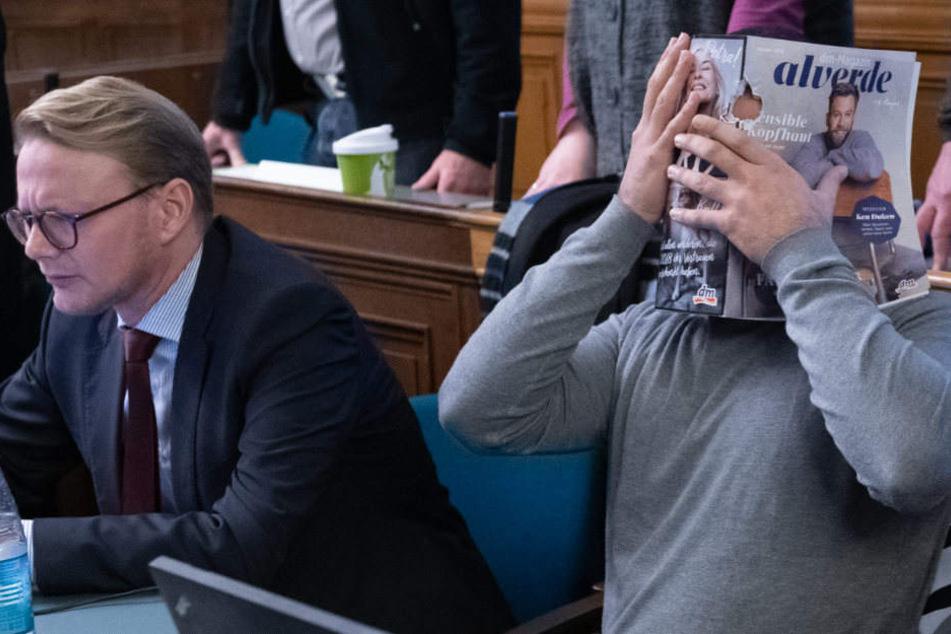 Einer der Angeklagten verdeckt sein Gesicht mit einer Zeitschrift.