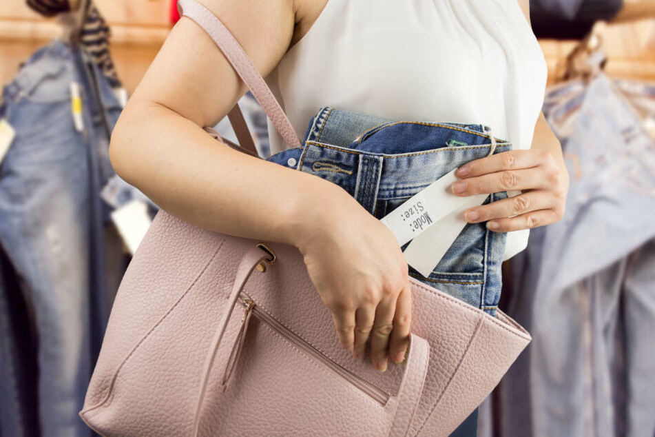 Eine Frau steckt heimlich eine Hose in ihre Handtasche. (Symbolbild)