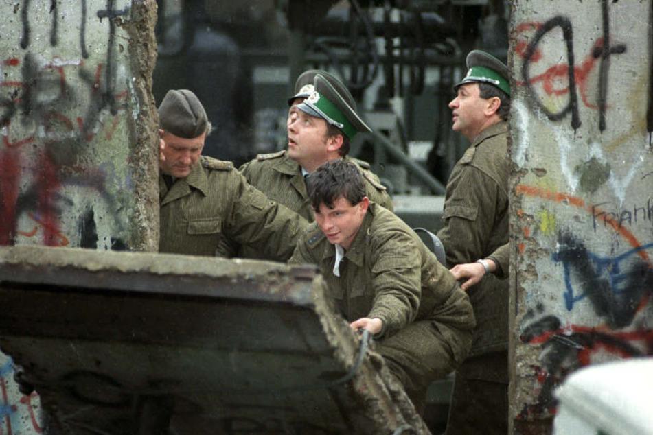 DDR-Grenzsoldaten schließen ein Loch, das Jugendliche in die Berliner Mauer gestemmt haben.