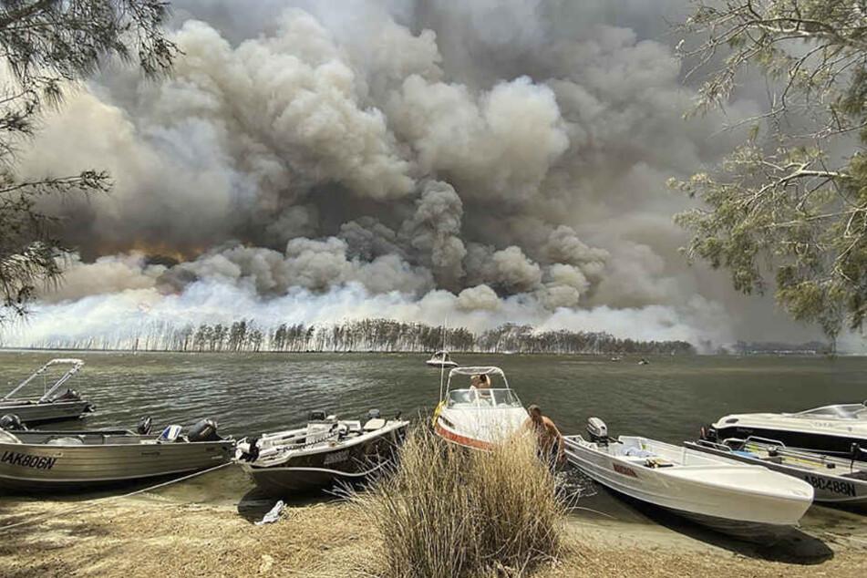 Boote werden an Land gezogen, während im Hintergrund Rauchwolken über dem Ufer hinter dem Canjola See aufsteigen.
