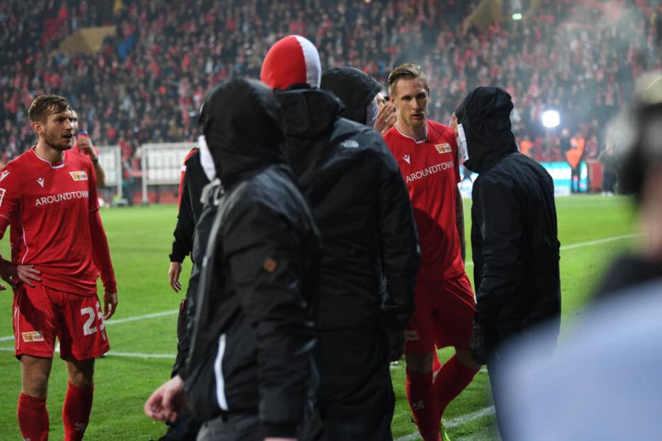 Unions Sebastian Polter (r) versucht nach dem Abpfiff und dem Sieg seines Teams im Derby vermummte Fans zu beschwichtigen.