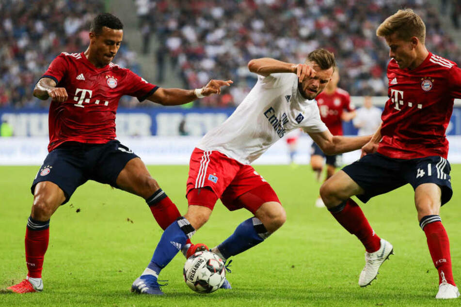 Hamburgs Manuel Wintzheimer und Münchens Thiago (l.) und Kilian Senkbeil (r.) kämpfen um den Ball.