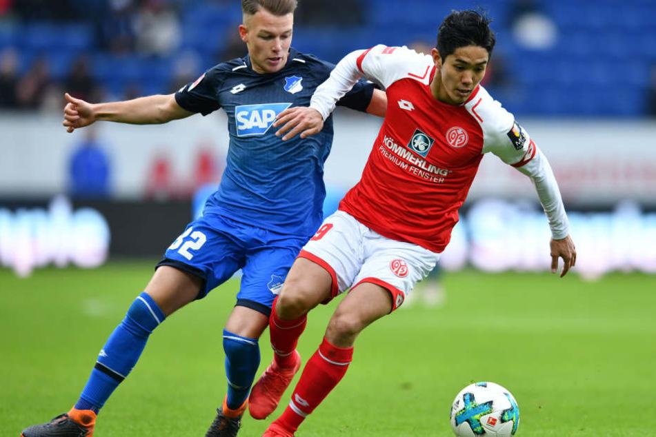 Hoffenheims Dennis Geiger (l.) und der Mainzer Yoshinori Muto kämpfen um den Ball.