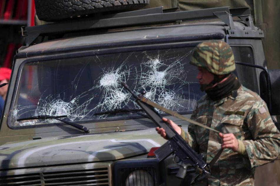 Ein griechischer Soldat patrouilliert am Grenzübergang in Kastanies neben einem Militärfahrzeug mit gebrochener Windschutzscheibe.