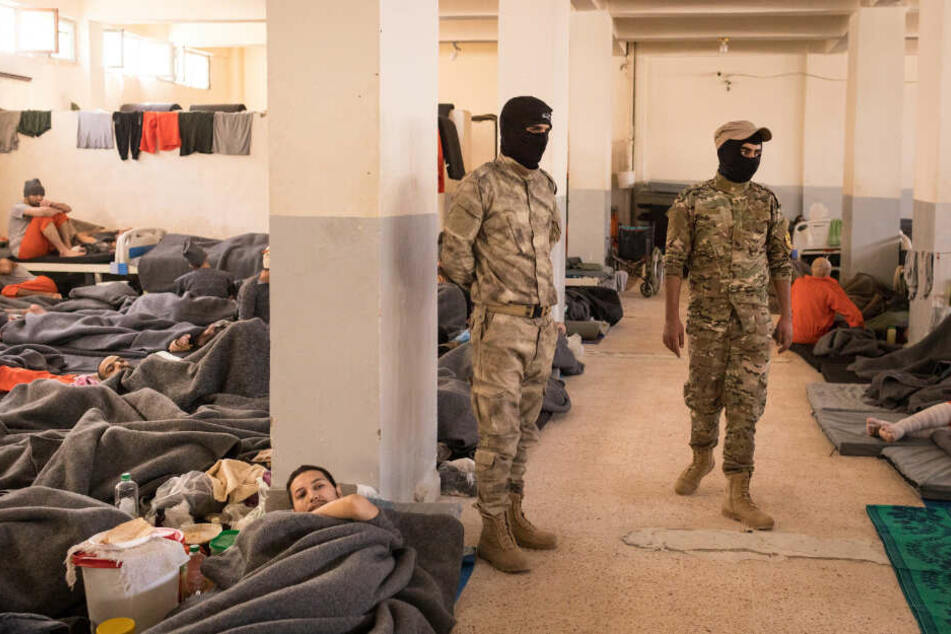 Zwei Männer bewachen zahlreiche Gefangene in orangenen Overalls, die in einem Raum in Hassake (Syrien) sitzen und liegen.