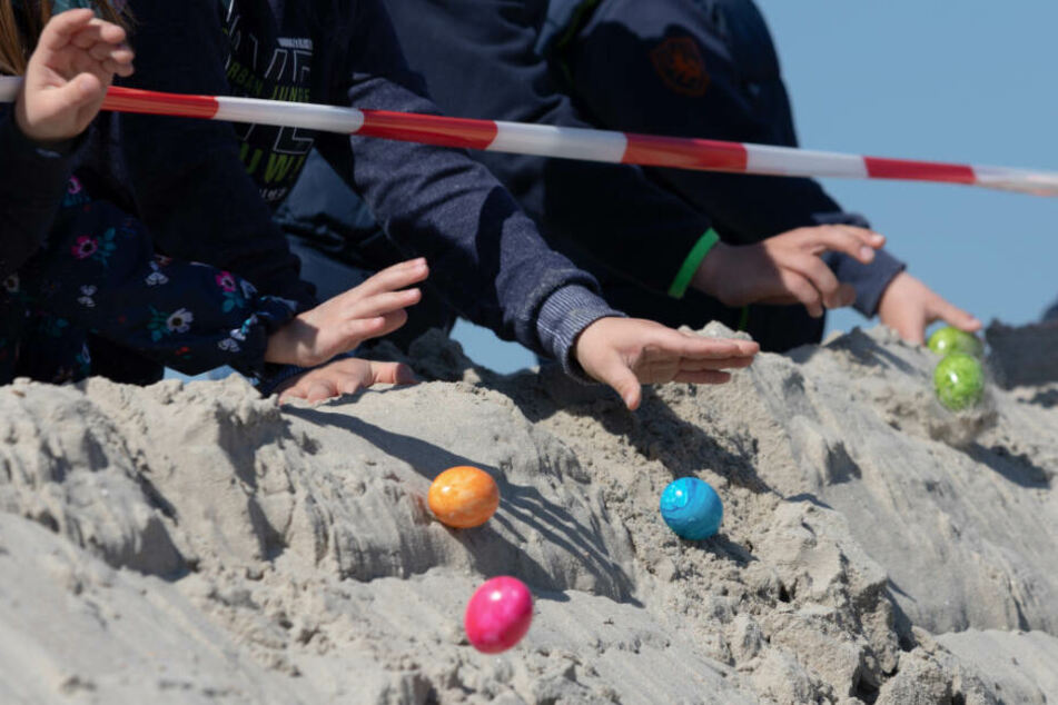 Kinder lassen Eier von einer Düne am Strand von Norderney heruntertrullern.