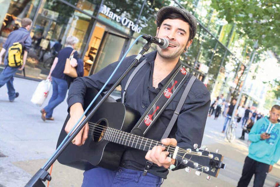 Sänger und Gitarrist Julien Zeke (36) spielt aktuell auf der Prager Straße ohne  aufwendige Genehmigungen. Ab nächstem Jahr soll eine Erlaubnis, per Smartphone  geordert, vorgeschrieben sein.