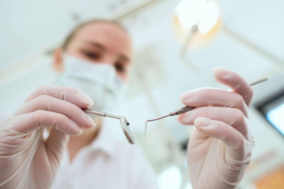 Eine Zahnarzthelferin hält Untersuchungswerkzeuge in der Hand.