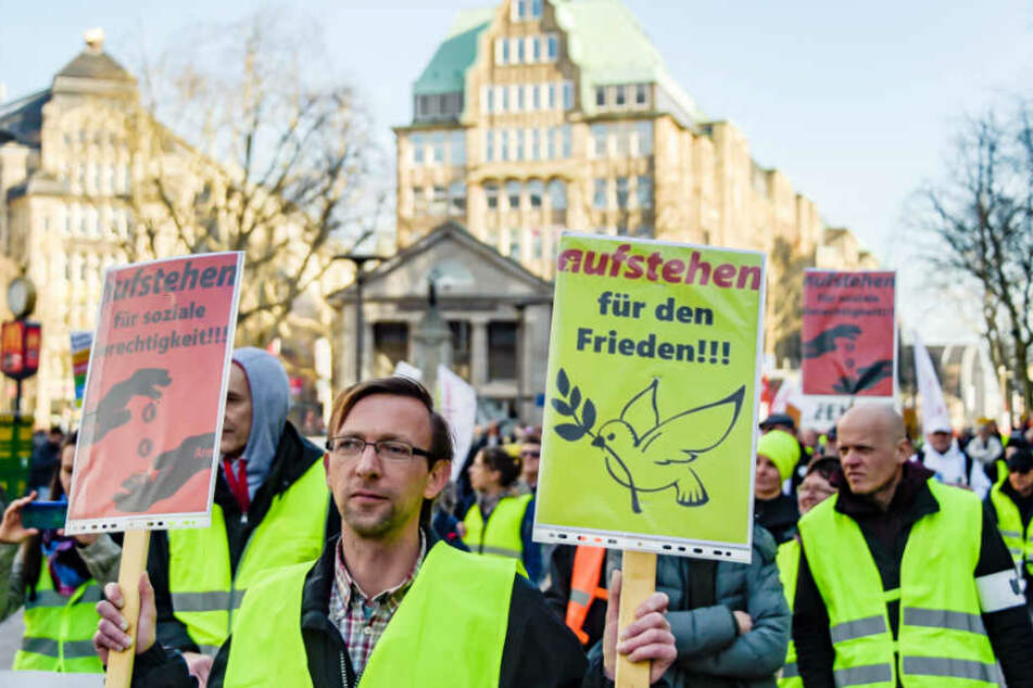 Mit Plakaten für soziale Gerechtigkeit und Frieden ziehen Menschen in gelben Westen während einer Demonstration durch Hamburg.