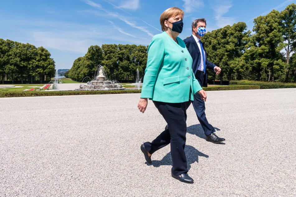 Markus Söder (CSU) und Bundeskanzlerin Angela Merkel (CDU) gehen nach einer gemeinsam Kutschfahrt zur Kabinettssitzung.