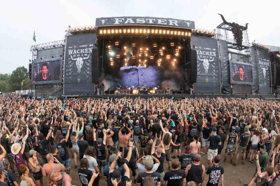 Festivalbesucher stehen vor einer der Hauptbühnen des Wacken Open Air Festivals.