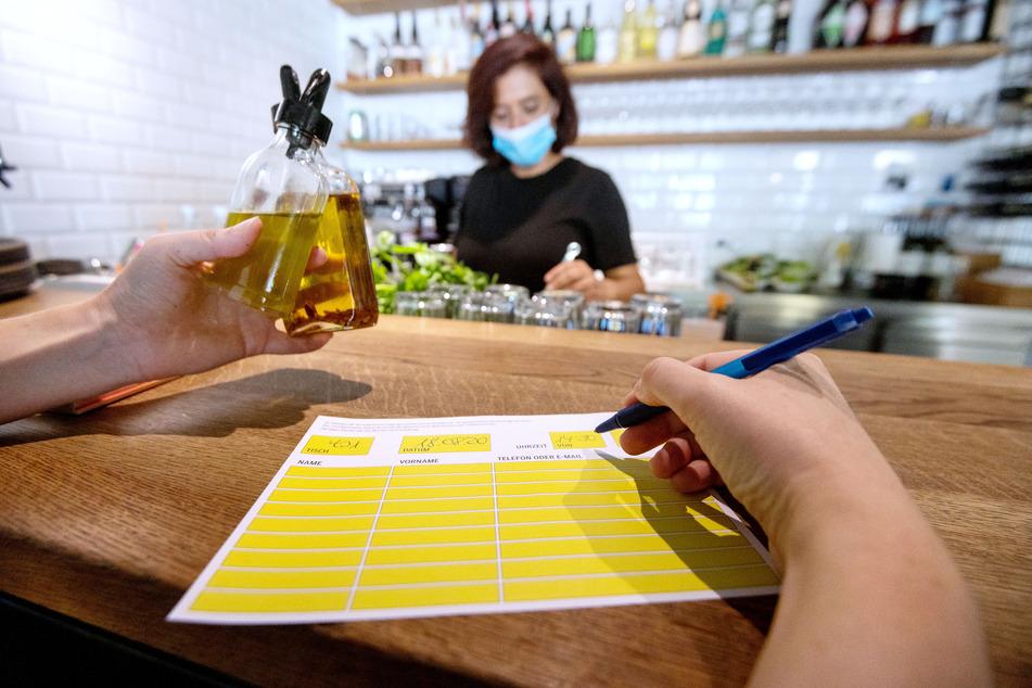 Eine Angestellte in einer Pizzeria hat einen Mundschutz an, während eine Kollegin auf der Theke ein Zettel zur Besucherregistrierung vorausfüllt.