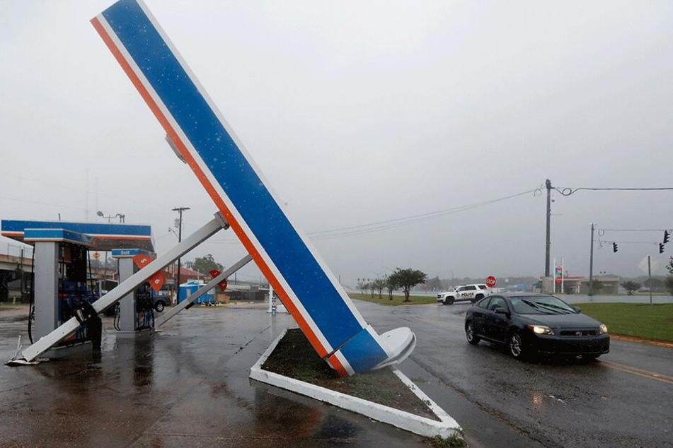 In der Ortschaft Berwick fährt ein Fahrzeug an der umgestürzten Zapfsäulen-Überdachung einer Tankstelle vorbei.