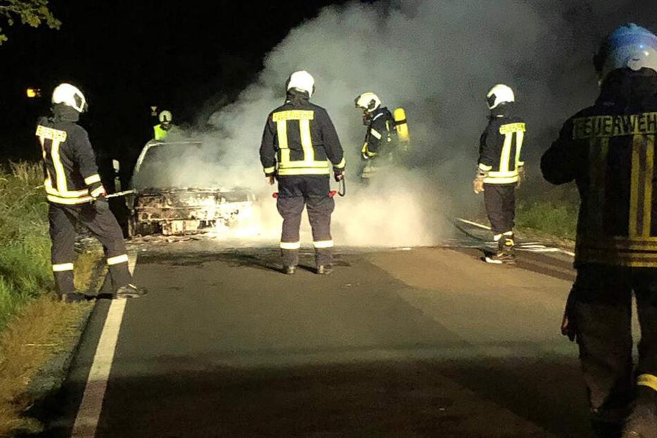 Die Einsatzkräfte löschen das Fahrzeug, welches augenscheinlich einen Totalschaden erlitten hat.