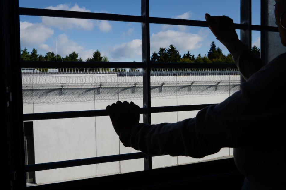 in Häftling steht in einer JVA an einem vergitterten Fenster in einer Zelle. (Symbolbild)