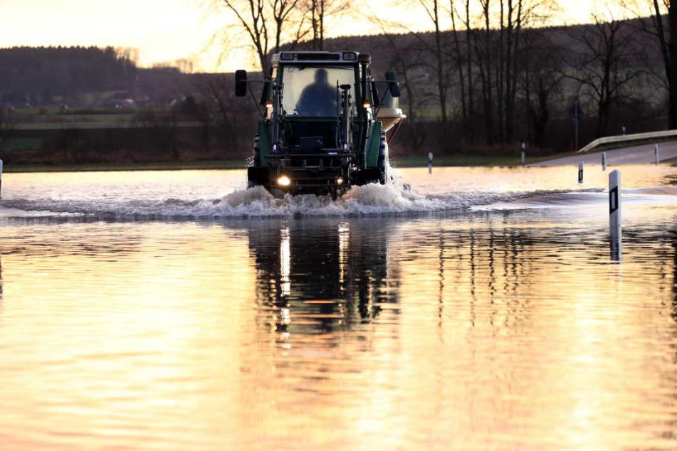 Ein Traktor fährt auf der überfluteten Kreisstraße nahe Unlingen (Kreis Biberach).